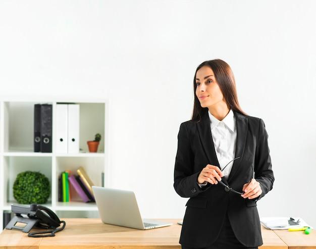Succesvolle jonge onderneemster die zich voor haar bureau bevindt