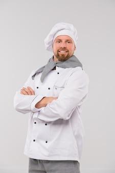 Succesvolle jonge professionele chef-kok van restaurant met zijn armen gekruist door de borst die zich voor de camera bevindt