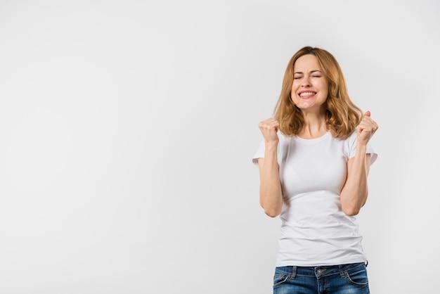Succesvolle jonge vrouw die na het winnen tegen witte achtergrond toejuichen