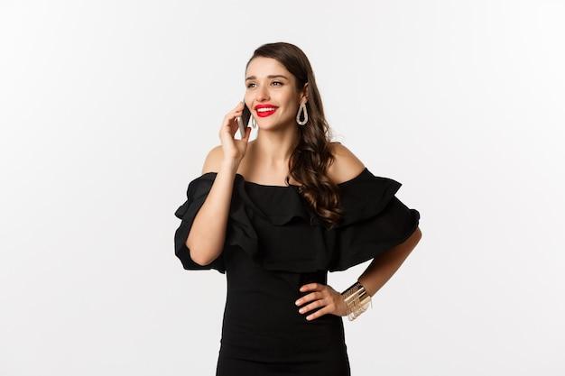 Succesvolle jonge vrouw in zwarte jurk, rode lippenstift en make-up, praten over de mobiele telefoon en glimlachen, staande op witte achtergrond.