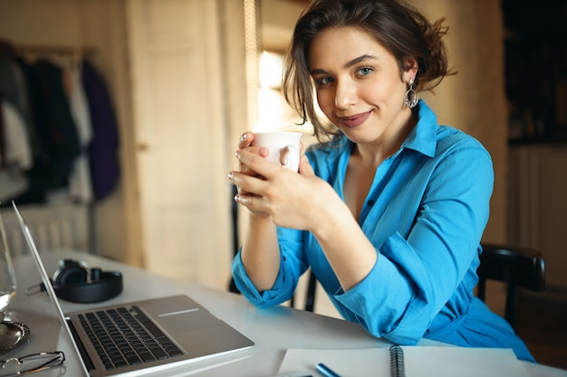 Succesvolle jonge vrouwelijke leraar in lijm jurk zit laptop, kopje houden, genieten van koffie, voorbereiden op online les, genieten van verre werk. mooi studentenmeisje dat draagbare computer met behulp van