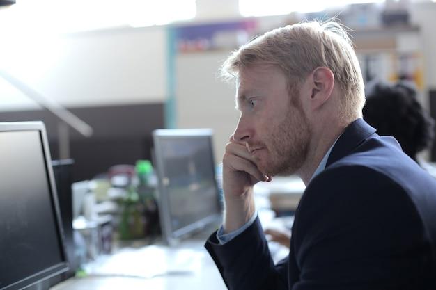 Succesvolle jonge zakenman die het computerscherm bekijkt dat in een modern startbureau werkt