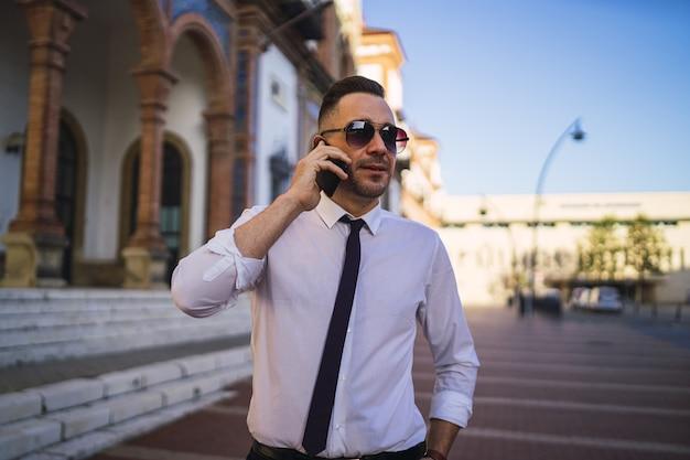 Succesvolle jonge zakenman in een formele outfit met zonnebril praten aan de telefoon