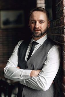 Succesvolle jonge zakenman in een vest en stropdas. met een stijlvol en stijlvol kapsel en een baard