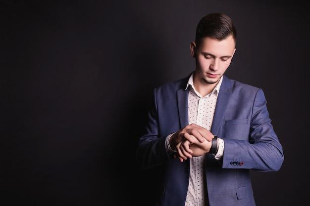 Succesvolle jonge zakenman in pak en wit overhemd en modieuze klok bij de hand op een zwarte achtergrond. stijlvolle man. beroepen voor mannen