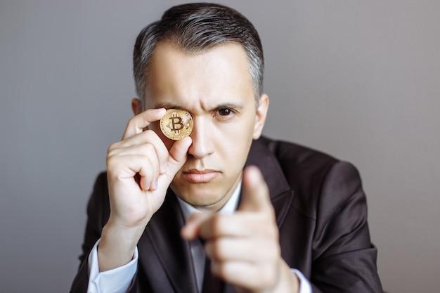 Succesvolle jonge zakenman in pak met bitcoin op grijs