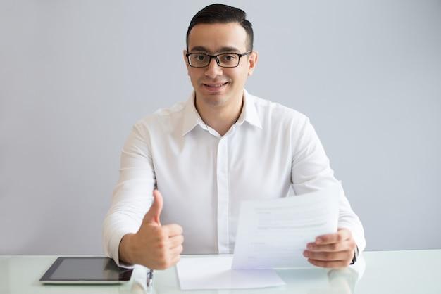 Succesvolle jonge zakenman met document duimen opdagen