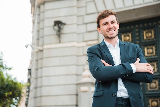 Succesvolle jonge zakenman met zijn gekruiste wapens status voor de bouw