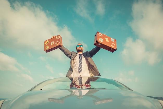 Succesvolle jonge zakenman op een strand man die in de klassieke auto van de cabriolet staat zomervakanties en vrijheidsreisconcept