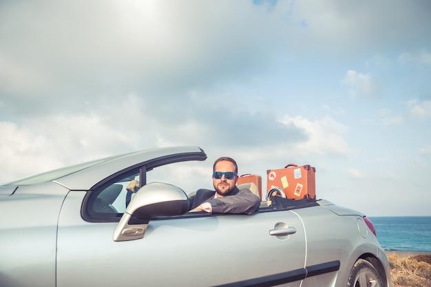 Succesvolle jonge zakenman op een strand man zit in de klassieke auto van de cabrio zomervakanties en reisconcept