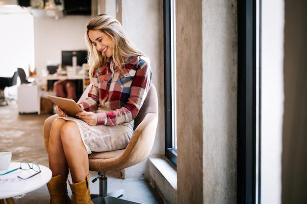 Succesvolle jonge zakenvrouw die op kantoor werkt
