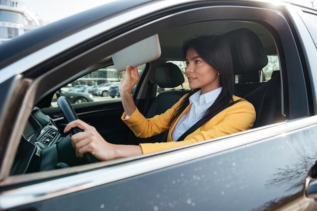 Succesvolle jonge zakenvrouw in gele jas zitten in haar auto