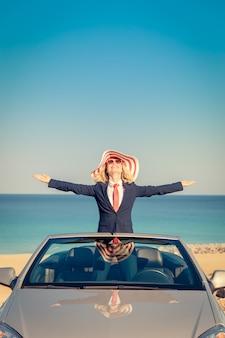 Succesvolle jonge zakenvrouw op het strand vrouw staat in de klassieke auto van de cabrio