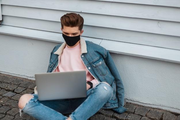 Succesvolle jongeman freelancer in beschermend zwart masker in stijlvolle denim kleding met laptop zit op stenen tegel in de buurt van vintage muur op straat. trendy man in modekleding man werkt op afstand. covid19.