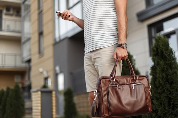 Succesvolle jongeman in een stijlvol t-shirt in modieuze korte broek met een vintage leren tas met een klok staat en kijkt naar de mobiel