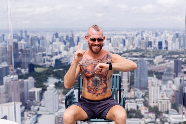 Succesvolle knappe europese bebaarde brute getatoeëerde sterke man topless met horloge zit op stoel op hoge verdieping met prachtig uitzicht op de stad