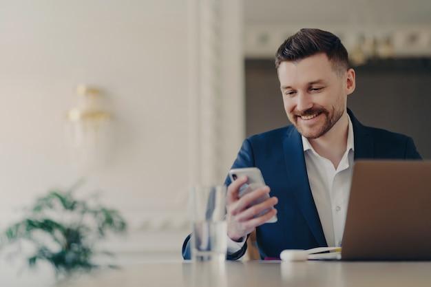 Succesvolle knappe executive manager in formeel pak kijkend naar smartphone en glimlachen tijdens het lezen van berichten of goed nieuws, zittend aan zijn bureau voor laptop in stijlvol kantoor
