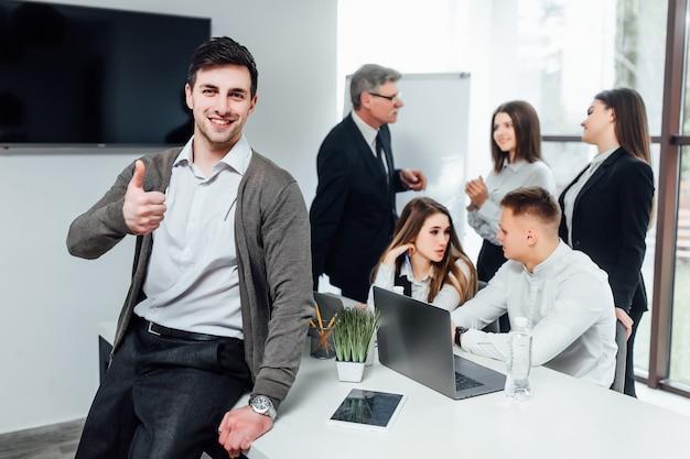 Succesvolle knappe zakenman verschijnt zijn vinger op moderne kantoor.