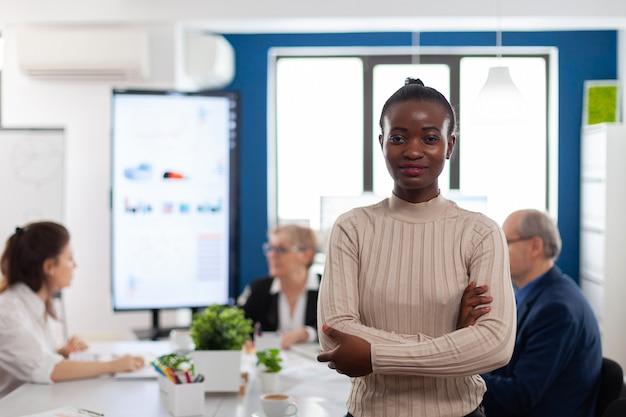 Succesvolle lachende afrikaanse zakenvrouw met gekruiste armen kijkend naar camera in vergaderruimte conference