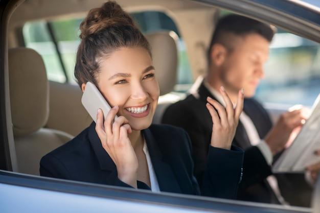 Succesvolle lachende vrouw praten op een smartphone in een auto
