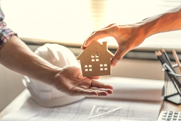 Succesvolle makelaar om het voltooide bouwproject over te dragen aan de koper van een woning