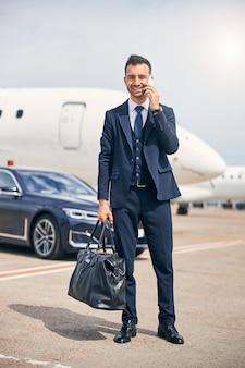 Succesvolle man die er zakelijk uitziet met een plunjezak die voor een vliegtuig staat