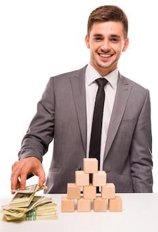 Succesvolle man houdt geld in zijn hand en glimlacht.