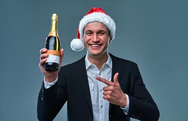 Succesvolle man in een jas en kerstmuts wijst een fles champagne viert nieuwjaar. studiofoto op een grijze achtergrond.