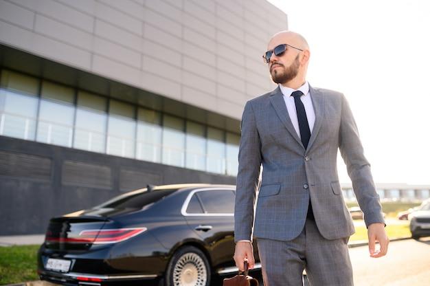 Succesvolle man in een pak met een koffer op de achtergrond van een dure auto