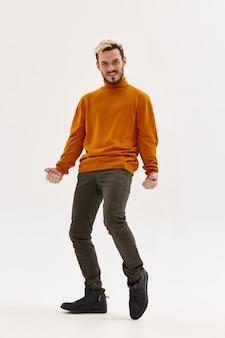 Succesvolle man in een trui en broek boog zijn knieën model van geluk. hoge kwaliteit foto