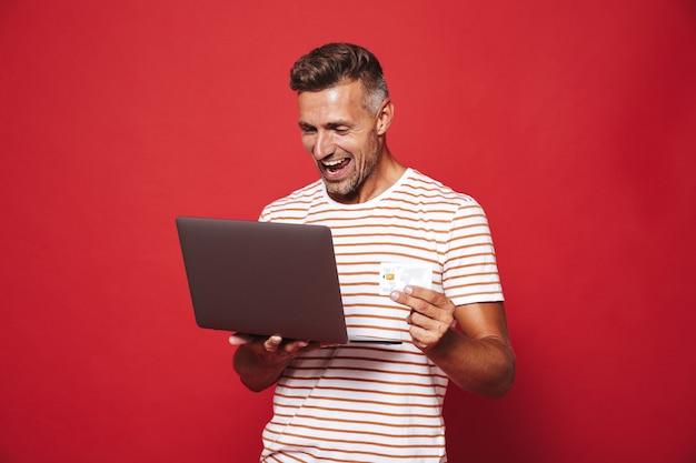Succesvolle man in gestreept t-shirt glimlachend terwijl hij een creditcard en laptop vasthoudt die op rood is geïsoleerd