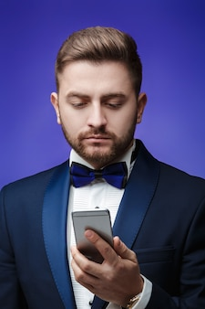 Succesvolle man in smoking en vlinderdas praten over telefoon zakenman smartphone blauw houden