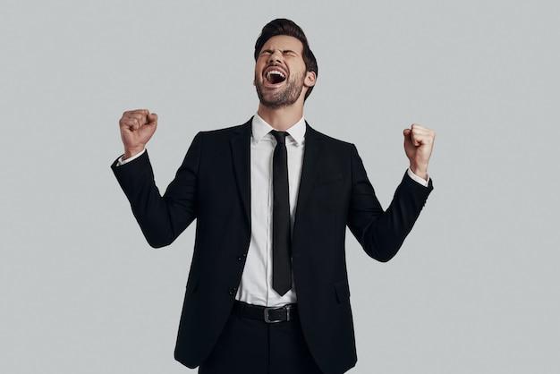 Succesvolle man. knappe jonge man in volledig pak gebaren en schreeuwen terwijl hij tegen een grijze achtergrond staat