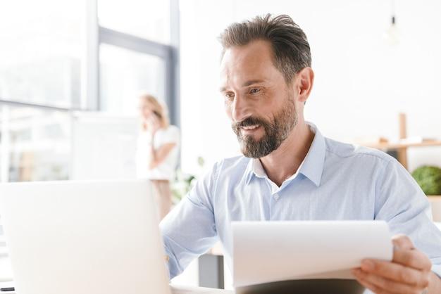 Succesvolle man manager die op laptopcomputer werkt