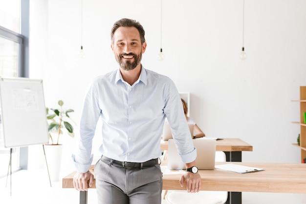 Succesvolle man manager leunend op een bureau
