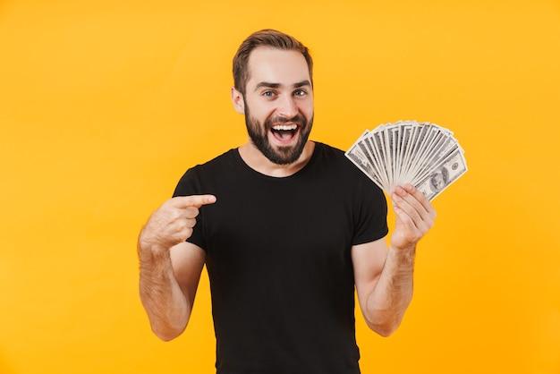 Succesvolle man met een zwart basic t-shirt glimlachend en met geld cash geïsoleerd over gele muur