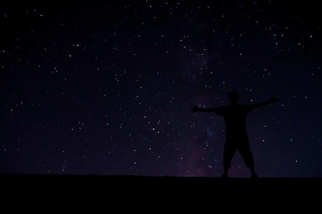 Succesvolle man op het hoogtepunt. onder de prachtige sterren aan de nachtelijke hemel.