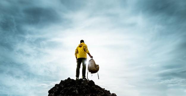 Succesvolle man staande op de top van de berg bij zonsondergang