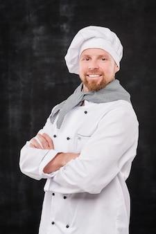 Succesvolle mannelijke chef-kok met zijn armen gekruist door de borst die naar je kijkt terwijl je tegen een zwarte achtergrond staat