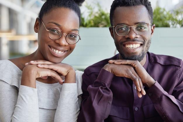 Succesvolle mannelijke en vrouwelijke collega's met een donkere huid hebben tevreden uitdrukkingen, ontvangen graag salaris of krijgen promotie op het werk, zitten dicht bij elkaar.