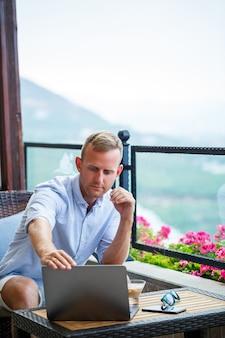 Succesvolle mannelijke zakenman die op vakantie werkt achter een laptop met uitzicht op de bergen. workflow voor onlinebeheer. buiten werken met een prachtig uitzicht vanaf het balkon