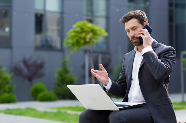 Succesvolle mannelijke zakenman meldt goed nieuws per telefoon, werkend met laptop tijdens de lunch in de buurt van kantoor zittend op de bank