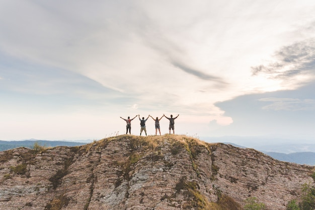 Succesvolle mensen met opgeheven armen op de top van een berg