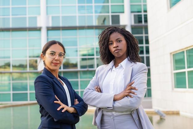 Succesvolle mix racete zakenvrouwen poseren met gekruiste handen