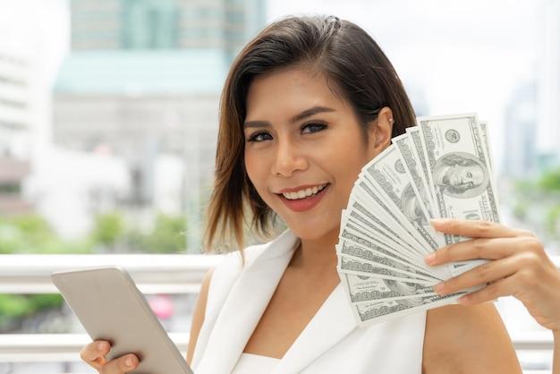 Succesvolle mooie aziatische bedrijfs jonge vrouw die slimme telefoon en geld amerikaanse dollarrekeningen ter beschikking gebruiken