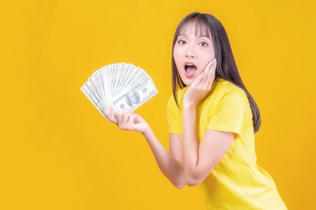 Succesvolle mooie aziatische zaken jonge vrouw met geld amerikaanse dollarbiljetten in de hand, bedrijfsconcept