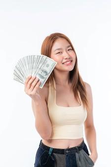 Succesvolle mooie aziatische zaken jonge vrouw met geld amerikaanse dollarbiljetten in de hand op een witte achtergrond, bedrijfsconcept
