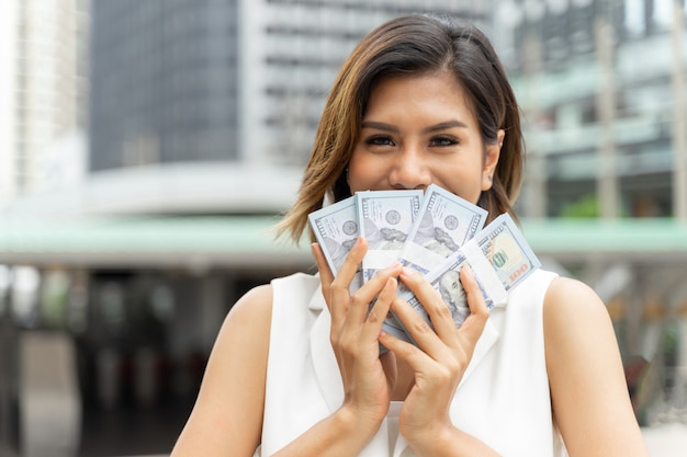 Succesvolle mooie aziatische zakenvrouw houden geld amerikaanse dollarbiljetten