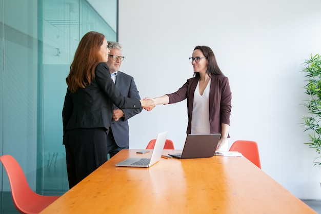 Succesvolle onderneemsters die elkaar de hand schudden en begroeten