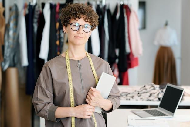 Succesvolle ondernemer en eigenaar van modestudio die zich in werkplaats bevindt